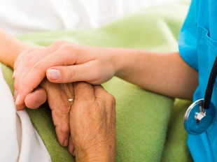 Social care provider holding senior hands in caring attitude - helping elderly people. ** Note: Shallow depth of field